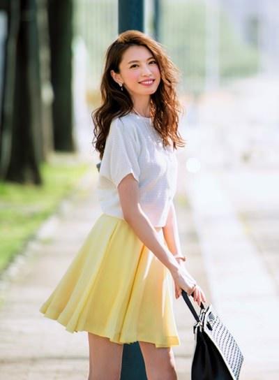 白いトップスにイエローのスカートを合わせたファッションの宮田聡子