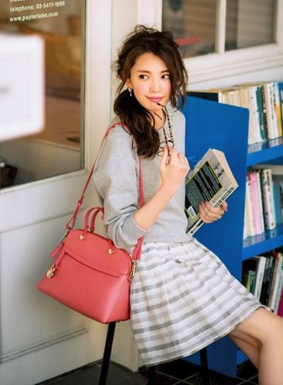 グレーでまとめたファッションの差し色にピンクのバッグを持つ宮田聡子